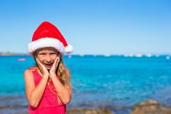 Suprised little girl in christmas hat during beach Royalty Free Stock Photography