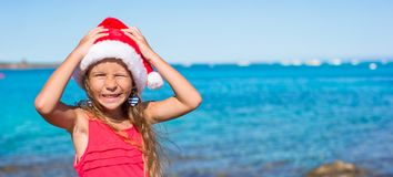 Suprised little girl in christmas hat during beach Stock Photos
