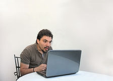 Suprised man. With black hair in front of lap top Stock Photography