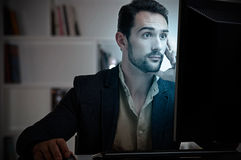 Suprised Man Looking At A Computer Monitor. Surprised man looking at a computer screen, in a dark room Stock Photos