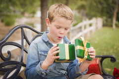Suprised Young Boy Opens Christmas Gift Outside Royalty Free Stock Image