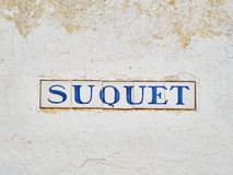 Suquet street signboard on a white stone wall. alella de Palafrugell, Spain. Calella de Palafrugell, Spain - September 15, 2018. Suquet street signboard on a royalty free stock images