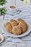 Sur des biscuits de farine d'avoine de plat avec des graines, fond en bois de lumière blanche photographie stock