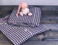 Sur des pyjamas à carreaux de flanelle de table en bois et un sommeil doucement images stock