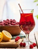 Sur en bois est le verre glacé de boisson avec le cocktail de framboise Images stock