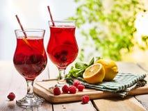Sur en bois sont les verres glacés avec le cocktail rouge de baies Photo libre de droits