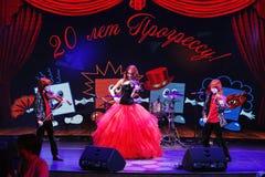 Sur l'étape, les fils roux expressifs de Maria Bessonova de violoniste jumelle générations du trio deux de violon des musiciens a Image stock