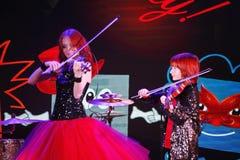 Sur l'étape, les fils roux expressifs de Maria Bessonova de violoniste jumelle générations du trio deux de violon des musiciens a Photographie stock libre de droits