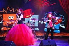Sur l'étape, les fils roux expressifs de Maria Bessonova de violoniste jumelle générations du trio deux de violon des musiciens a Photographie stock