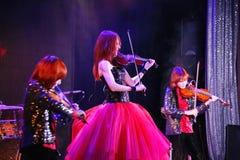 Sur l'étape, les fils roux expressifs de Maria Bessonova de violoniste jumelle générations du trio deux de violon des musiciens a Photo stock