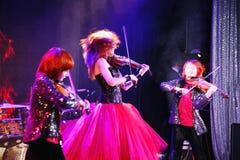 Sur l'étape, les fils roux expressifs de Maria Bessonova de violoniste jumelle générations du trio deux de violon des musiciens a Photos stock