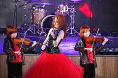 Sur l'étape, les fils roux expressifs de Maria Bessonova de violoniste jumelle générations du trio deux de violon des musiciens a Photo libre de droits