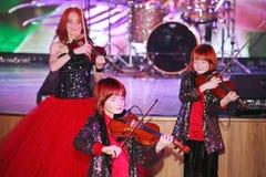 Sur l'étape, les fils roux expressifs de Maria Bessonova de violoniste jumelle générations du trio deux de violon des musiciens a Images stock