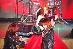 Sur l'étape, les fils roux expressifs de Maria Bessonova de violoniste jumelle générations du trio deux de violon des musiciens a Photos libres de droits