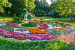 Sur l'herbe verte en parc une belle composition des fleurs et des personnages de dessin animé au milieu à côté de la maison Photos libres de droits