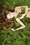 Sur l'herbe verte est une fille avec de beaux cheveux photographie stock