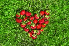 Sur l'herbe verte selon l'opinion du coeur a étendu l'endroit rouge de fraise pour la configuration d'appartement d'inscription Photos stock