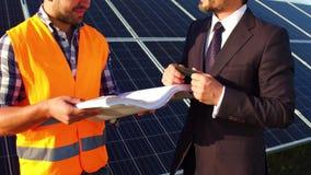 Sur l'ingénieur et l'homme d'affaires de longueur discutant les dessins techniques, panneaux solaires derrière eux banque de vidéos