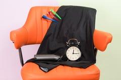 Sur l'orange la chaise est un ensemble d'objets pour créer une coiffure et un réveil noir photos libres de droits