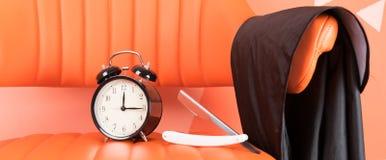 Sur l'orange une chaise est un ensemble de raser des articles et un réveil noir images libres de droits