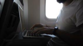 Sur l'ordinateur portable dans l'avion il y a un passager sur des affaires par voyage banque de vidéos