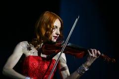Sur la belle, fragile et mince fille d'étape - avec les cheveux rouges ardents - un musicien bien connu, violoniste Maria Bessono Image stock