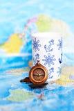 Sur la boussole et la tasse de carte du monde Image stock
