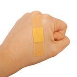 Sur la main d'un homme le poing a collé l'annonce médicale de plâtre de premiers secours de plâtre images libres de droits