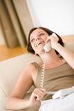 Sur la maison de téléphone : Femme de sourire sur sofa appelle Photos stock