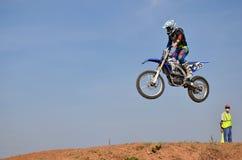 Sur la moto un cavalier saute par-dessus un haut monticule de la terre Photo stock
