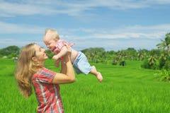 Sur la mère verte de fond de terrasses de riz jetant le bébé garçon en l'air joyeux Photographie stock