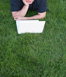 Sur la pelouse, sur le coude avec l'ordinateur portatif photographie stock
