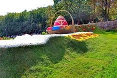 Sur la pelouse verte en parc une exposition sur le thème des coutumes folkloriques Un oeuf grand décoré des modèles dans un osier Images libres de droits