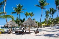 Sur la plage il y a des maisons de paille sur le fond des palmiers et d'un beau ciel bleu Photos libres de droits