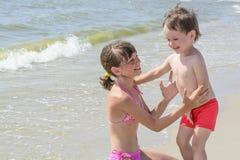 Sur la plage la soeur plus âgée veut étreindre un frère de bébé, et contre le contexte de la mer ondule Photographie stock