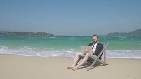 Sur la plage le jeune homme derrière l'ordinateur portable fait des affaires en vacances banque de vidéos