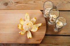 Sur la planche à découper en bois est l'orange épluchée, à côté de trois verres avec des morceaux de banane Photo libre de droits