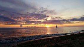 Sur la r?flexion du soleil en mer, les silhouettes des personnes sont ?videntes, pendant un coucher du soleil magnifique de coule banque de vidéos