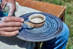 Sur la roue du ` s de potier tournez une rotation d'une tasse d'argile image libre de droits