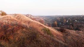 Sur la sépia d'automne et les collines oranges avec de petits arbustes Photographie stock libre de droits