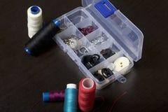 Sur la surface de la table est une boîte avec les accessoires de couture Plusieurs bobines de fil se trouvent l'un à côté de l'au Photos stock