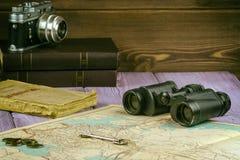 Sur la table étendue un vieux livre, carte, pièces de monnaie, une clé et des jumelles Il y a également un appareil-photo de film photo stock