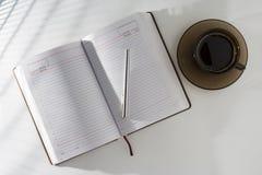 Sur la table dans un journal intime et un stylo ouverts, se tenant à côté d'une tasse de café Image libre de droits