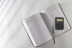 Sur la table dans un journal intime ouvert et un stylo avec une calculatrice Photos stock