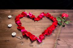 Sur la table en bois, à la gauche du coeur des lepistas des roses il y a des bougies Image stock