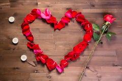 Sur la table en bois, à la gauche du coeur des lepistas des roses il y a des bougies, et vers la droite il y a une rose de rose Image libre de droits