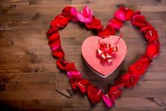 Sur la table en bois, à l'intérieur du coeur des lepistas des roses est une boîte avec un cadeau sous forme de coeur Copiez l'esp Photographie stock