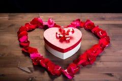 Sur la table en bois, à l'intérieur du coeur des lepistas des roses est une boîte avec un cadeau sous forme de coeur Copiez l'esp Images stock