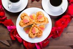 Sur la table en bois, à l'intérieur du coeur des pétales de rose sont deux Photographie stock libre de droits