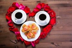 Sur la table en bois, à l'intérieur du coeur des pétales de rose sont deux Images stock